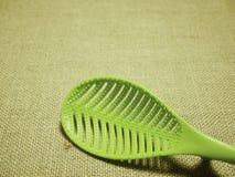 在麻袋布被编织的背景的绿色塑料杓子 免版税库存照片