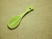 在麻袋布被编织的背景的绿色塑料杓子 库存照片