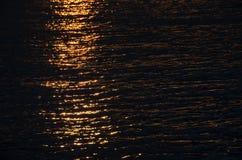 在黄昏期间的黑暗的水与表面上的强光从太阳 图库摄影