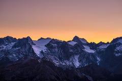 在黄昏的五颜六色的天空在断层块des Ecrins的庄严峰顶的冰川之外4101 m,法国 从dist的远距照相视图 免版税图库摄影