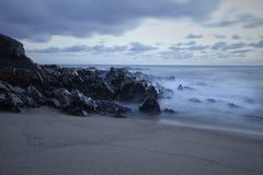 在黄昏的岩石海景 免版税库存图片