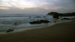 在黄昏的岩石海海滩 免版税图库摄影