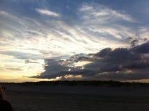 在黄昏的海滩与明亮的云彩 免版税库存照片