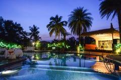 在黄昏的游泳池边热带度假胜地 库存图片