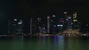 在黄昏的Merlion雕象与2016年11月18日的bussiness大厦在新加坡 股票视频