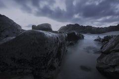 在黄昏,蓝色小时的喜怒无常的海景 免版税库存照片