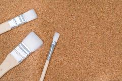 在黄柏板的三支不同白色画笔 库存图片