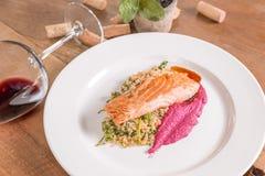 在黄油的盐味的三文鱼用奎奴亚藜和紫罗兰色调味汁 免版税库存图片