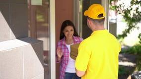在黄色制服的传讯者交付比萨箱子到妇女在门道入口 影视素材