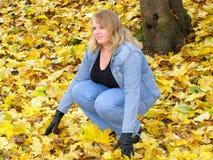 在黄色叶子中的女孩 免版税库存图片