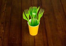 在黄色塑料杯子的绿色一次性叉子,木表面上 免版税库存照片