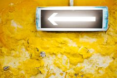 在黄色墙壁上的一个箭头 库存照片