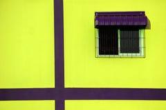 在黄色墙壁上的窗口 免版税库存照片