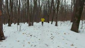 在黄色外套训练的幼小有胡子的赛跑者在森林里在寒冷冬天天 股票视频