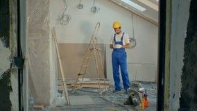 在黄色安全工程师盔甲的年轻男性使用手机或发短信在建造场所 影视素材