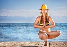 在黄色帽子的瑜伽 库存图片