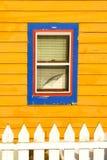 在黄色房子的蓝色窗口 免版税图库摄影