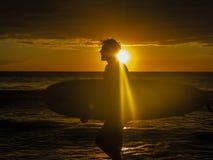 在黄色日落用灿烂光辉包括一切的海滩的Sihouetted冲浪者运载的冲浪板 图库摄影