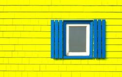 在黄色木墙壁上的窗口 库存图片