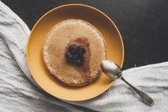 在黄色板材的自创薄煎饼用樱桃果酱 免版税图库摄影