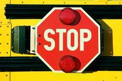 在黄色校车的红色停车牌 免版税库存照片