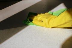 在黄色橡胶手套洗涤的表面的手 大扫除 E 免版税库存照片