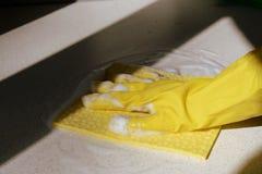 在黄色橡胶手套洗涤的表面的手 大扫除 E 免版税图库摄影