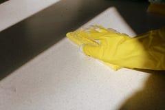 在黄色橡胶手套洗涤的表面的手 大扫除 E 免版税库存图片