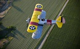 在黄色的双翼飞机领域 免版税库存图片