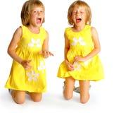 在黄色礼服的姐妹孪生 免版税库存图片