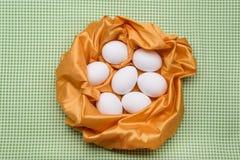在黄色纹理抽象巢的白鸡蛋,绿色 库存图片