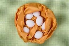 在黄色纹理抽象巢,桌布绿色背景的白鸡蛋在厨房里 免版税图库摄影