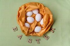 在黄色纹理抽象巢,桌布绿色背景的白鸡蛋在厨房里 库存图片