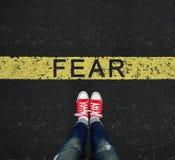 在黄色罗阿写的恐惧标志前面的年轻身分 库存照片