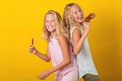 在黄色背景一起孪生获得少年的女孩乐趣,隔绝 免版税库存照片