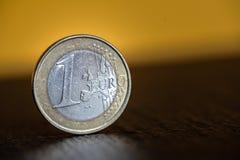 在黄色背景的一枚欧洲硬币 库存图片