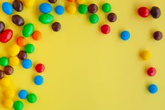 在黄色背景的五颜六色的糖果 库存图片