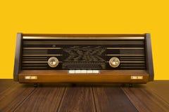 在黄色背景的古色古香的收音机与木的黑褐色 免版税库存图片