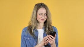 在黄色背景的年轻俏丽的女孩浏览智能手机 股票录像