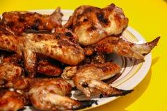 在黄色背景的油煎的鸡翅 免版税库存图片