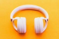 在黄色背景的浅粉红色的时尚耳机 免版税库存图片