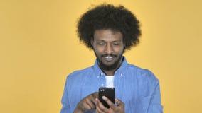 在黄色背景的美国黑人的人浏览智能手机 影视素材