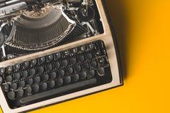 在黄色背景的老打字机,顶视图 创造性的新闻事业概念 库存照片