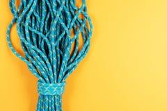 在黄色背景的蓝色绳索 库存图片