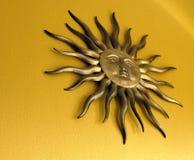 在黄色背景的金黄金属太阳墙壁装饰 免版税库存照片