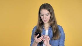 在黄色背景隔绝的俏丽的妇女浏览智能手机 影视素材