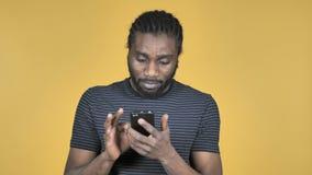 在黄色背景隔绝的偶然非洲人浏览智能手机 股票视频