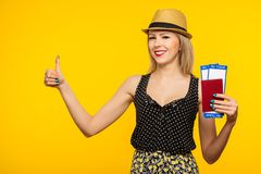 在黄色背景隔绝的年轻微笑的激动的女学生藏品护照登机牌票 教育在大学 免版税库存照片