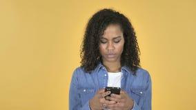 在黄色背景隔绝的非洲女孩浏览智能手机 股票视频