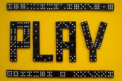 在黄色背景,戏剧的多米诺片断 库存图片